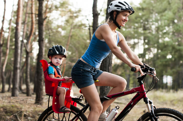 Mother riding on bicycle with young child in back